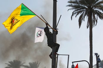 A member of Hashd al-Shaabi holds a flag of the Kataib Hezbollah militia group during a protest in Baghdad, Iraq on December 31, 2019.