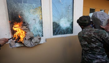 Members the Iran-backed Shiite militia network Hashed al-Shaabi smash the bullet-proof glass of the U.S. embassy's windows in Baghdad after breaching the outer wall of the diplomatic mission, December 31, 2019