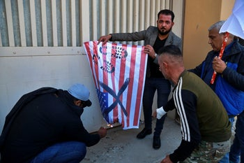 Iran-backed Popular Mobilization Forces and their supporters burning representations of a U.S. flag in front of the U.S. Embassy in Baghdad, December 31, 2019.