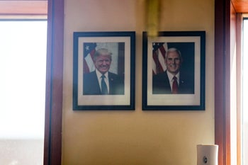 Photographs of U.S. President Donald Trump and Vice President Mike Pence hanging on a wall inside of the security office at the entrance of the U.S. Embassy building in Baghdad, December 31, 2019.