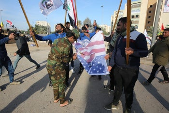 Supporters and members of the Hashed al-Shaabi paramilitary force burning the U.S. flag during a demonstration outside the U.S. Embassy in Baghdad, Iraq, January 1, 2020.