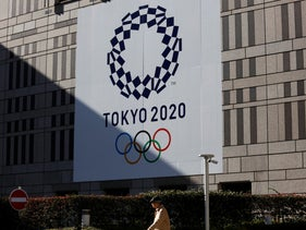 A man walks past a large Tokyo 2020 banner hanging on the facade of the Tokyo Metropolitan Government building, Nov. 21, 2019, in Tokyo.