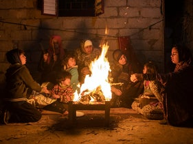 A Palestinian family warm themselves by a fire during a cold weather spell in a slum on the outskirts of the Khan Younis refugee camp, southern Gaza Strip, Dec. 31, 2019.