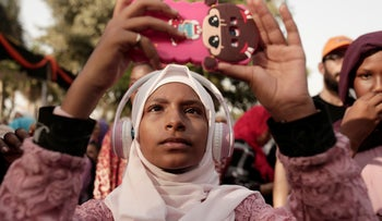 A teenager films Sudanese dancers on her mobile phone during an event marking the UN's International Refugee Day, in Cairo, Egypt, June 20, 2019.