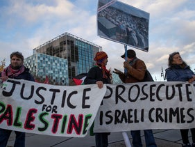 Demonstrators carry banners outside the International Criminal Court, urging the court to prosecute Israel's army for war crimes, in The Hague, Netherlands, Nov. 29, 2019.
