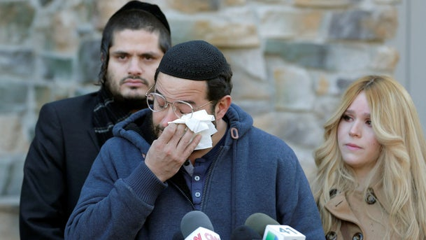 Surrounded by family, David Neumann wipes his eyes as he speaks to reporters on Jan. 2, 2020, about his father, Josef Neumann, critically injured and still unconscious in an attack on a Hanukkah celebration