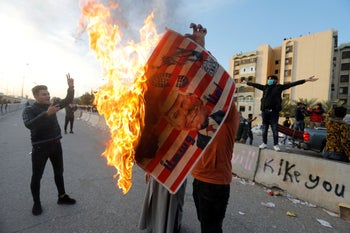 A protester holds a placard with U.S. President Donald Trump illustration burning outside the U.S. Embassy Baghdad, Iraq January 1, 2020.