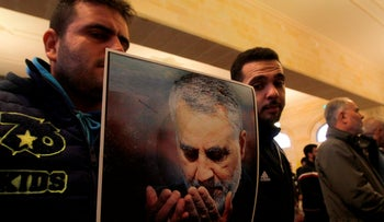 Supporters of Lebanon's Hezbollah hold a picture of Qassem Soleimani, who was killed in a US air strike in Baghdad, during a mourning prayer in a mosque in the southern town of Ghazieh, Lebanon, January 3, 2020