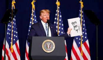 U.S. President Donald Trump holds a sign depicting 'Never give up!' as he gives his speech to evangelical supporters in Miami, Florida, U.S., January 3, 2020.