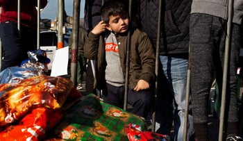 A little boy waits for a Christmas present as anti-government protesters distribute gifts to the needy, at Martyrs' Square in Beirut, Lebanon,on December 22, 2019.