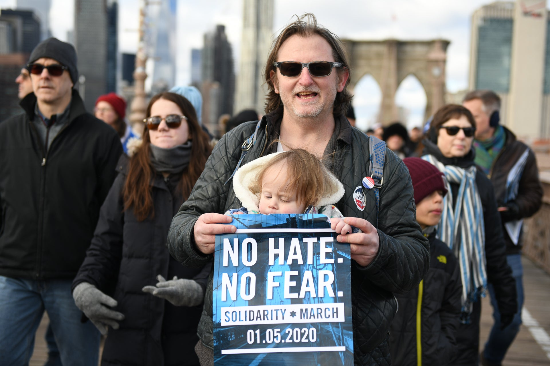 A man carries a small child during a march against anti-Semitism, New York City, January 5, 2019