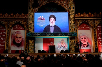 Hezbollah supporters watch as Nasrallah delivers a speech on a screen, Beirut, January 5, 2020.