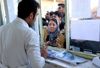 A woman shows a medic a picture of her brother as people queue to check if their loved ones are alive or dead following a stampede in Kerman, Iran, on January 7, 2020