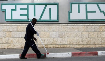 A man cleans near the logo of Teva Pharmaceutical Industries at their plant in Jerusalem, December 14, 2017