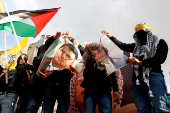 Supporters of the Palestinian Fatah movement burn a picture of exiled Palestinian politician Mohammed Dahlan in Bethlehem on January 1, 2020.
