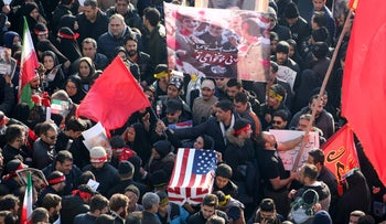 Iranian mourners carry a symbolic coffin wrapped in a U.S. flag during the funeral procession of General Qasem Soleimani in the capital Tehran on January 6, 2020.