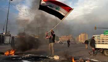 A protester waves the national flag while demonstrators set fire to close streets near Tahrir Square during a demonstration against the Iranian missile strike in Baghdad, Iraq, Wednesday, Jan. 8, 2020