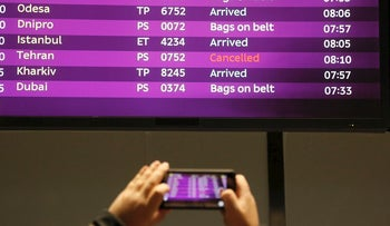 A man takes a photo of the arrivals board with the cancelled fight from Tehran after Ukrainian 737-800 plane crashed on the outskirts of Tehran, Iran, at Borispil international airport outside Kyiv, Ukraine, Wednesday, Jan. 8, 2020.