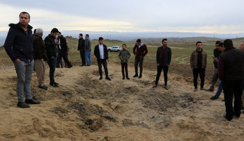 Residents look at a crater caused by a missile launched by Iran on U.S.-led coalition forces on the outskirts of Duhok, Iraq, January 8, 2020