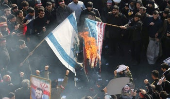 Iranians set a U.S. and an Israeli flag on fire during a funeral procession for military commander Qassem Soleimani, Iraqi paramilitary chief Abu Mahdi al-Muhandis and other victims of a U.S. attack, Tehran, January 6, 2020.