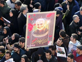 Iranian mourners lift a picture of slain military commander Qassem Soleimani during a funeral procession in the capital Tehran on January 6, 2020.