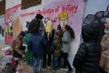 Youngsters surrounding two activists painting the mural in Idlib Province, Syria, inspired by the January 3, 2020, killing of Qassem Soleimani in Iraq.