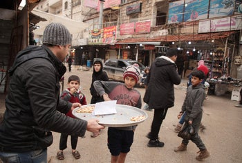 A Syrian man in the rebel-held town of Dana, Idlib, offering sweets to children to mark the killing on January 3, 2020 of Qassem Soleimani in Baghdad.