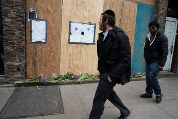 Men pass the boarded-up kosher supermarket in Jersey City, New Jersey, where three people and the two gunmen were killed days earlier, December 13, 2019.