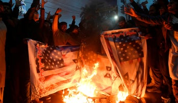 Pakistani Shiite Muslim burn US and Israeli flags in a protest against the killing of top Iranian commander Qasem Soleimani in the US strike in Iraq, in Lahore on January 7, 2020