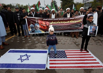 Shiite Muslims children stand on representations of Israeli and U.S. flags during a rally to condemn the killing of Iranian Revolutionary Guard Gen. Qassem Soleimani. Islamabad, Pakistan, Jan. 5, 2020