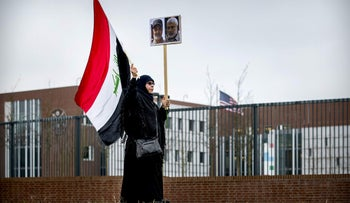 A protester holds an Iraqi flag and portraits of Iranian commander Qasem Soleimani (L) and Abu Mahdi al-Muhandis outside the US Embassy in The Hague, January 7, 2020.