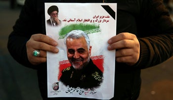 A man holds a picture of slain Iranian Major-General Qassem Soleimani, as people celebrate in the street after Iran launched missiles at U.S.-led forces in Iraq, Iran January 8, 2020.