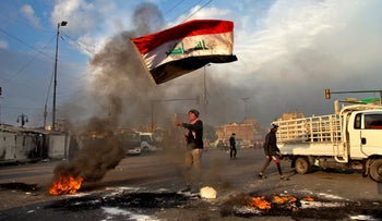 A protester waves the national flag during a demonstration against the Iranian missile strike in Baghdad, Iraq, January 8, 2020.