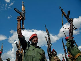 Sudan People's Liberation Army (SPLA) soldiers raise their rifles at a containment site outside of Juba on April 14, 2016.