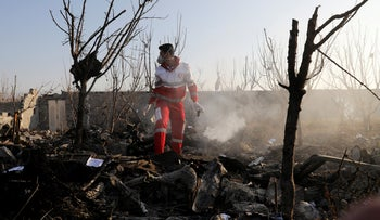 A rescue worker searches the scene where an Ukrainian plane crashed in Shahedshahr, southwest of the capital Tehran, Iran, Jan. 8, 2020.