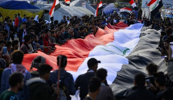 Iraqi anti-government demonstrators deploy a giant national flag as they protest in the central city of Najaf, on January 10, 2020.