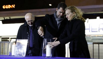 French Interior Minister Christophe Castaner and Justice Minister Nicole Beloubet light a candle next to CRIF President Francis Kalifat (L), outside the Hyper Cacher kosher supermarket in Paris, France, January 9, 2020.