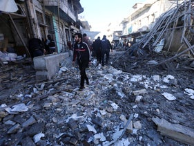 People walk though Idlib city center after it was hit by airstrikes, January 11, 2020.