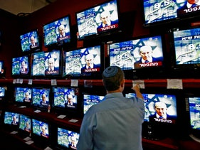 A man shops for televisions as Israeli Prime Minister Ehud Olmert is seen on a news program at an electronics shop in Jerusalem, Sunday, Sept. 21, 2008.