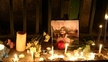 A picture is seen next to candles lit by people and families of the victims of the crash of the Boeing 737-800 plane, flight PS 752, in Tehran, Iran January 11, 2020.