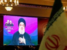 Hezbollah supporters watch as Hasan Nasrallah delivers a speech on a screen in the southern Lebanese city of Nabatieh on January 12, 2020.