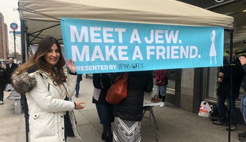 """Allison Josephs standing next to her """"Meet a Jew, Make a Friend"""" canopy tent in East Harlem, New York, January 13, 2020."""