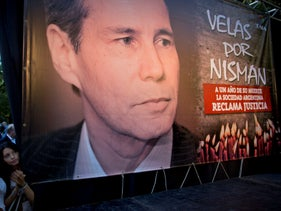 """Women stand beside a picture of late prosecutor Alberto Nisman that reads in Spanish """"Candles for Nisman,"""" on the one-year anniversary of his death in Buenos Aires, Argentina,on January 18, 2016."""