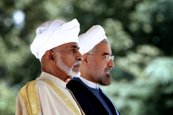 Iranian President Hassan Rouhani (R) and Oman's Sultan Qaboos bin Said listen to the national anthems at Tehran's Saadabad Palace. August 25, 2013