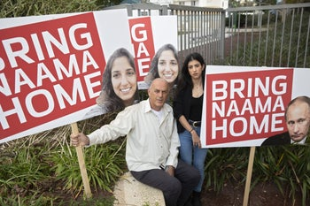 """Israel Cohen, left, and Liad Goldberg holding placards saying """"Bring Naama Home,"""" Rehovot, January 14, 2020."""