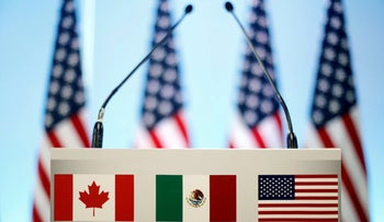 The flags of Canada, Mexico and the U.S. are seen on a lectern before a joint news conference on the closing of the seventh round of NAFTA talks in Mexico City, Mexico, on March 5, 2018.