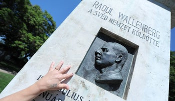A Hungarian woman touches the memorial stone of Wallenberg in Budapest on August 1, 2012.