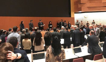 Delegates gather around an empty screen at a meeting on lethal autonomous weapons in the United Nations in Geneva, Switzerland in this picture released to Reuters and taken November 15, 2019