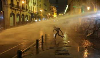 A demonstrator is hit by a water cannon during a protest against a ruling elite accused of steering Lebanon towards economic crisis in Beirut, Lebanon January 19, 2020