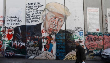 A Palestinian man walking past a vandalized mural painting of U.S. President Donald Trump on the West Bank separation barrier in Bethlehem, January 3, 2020.